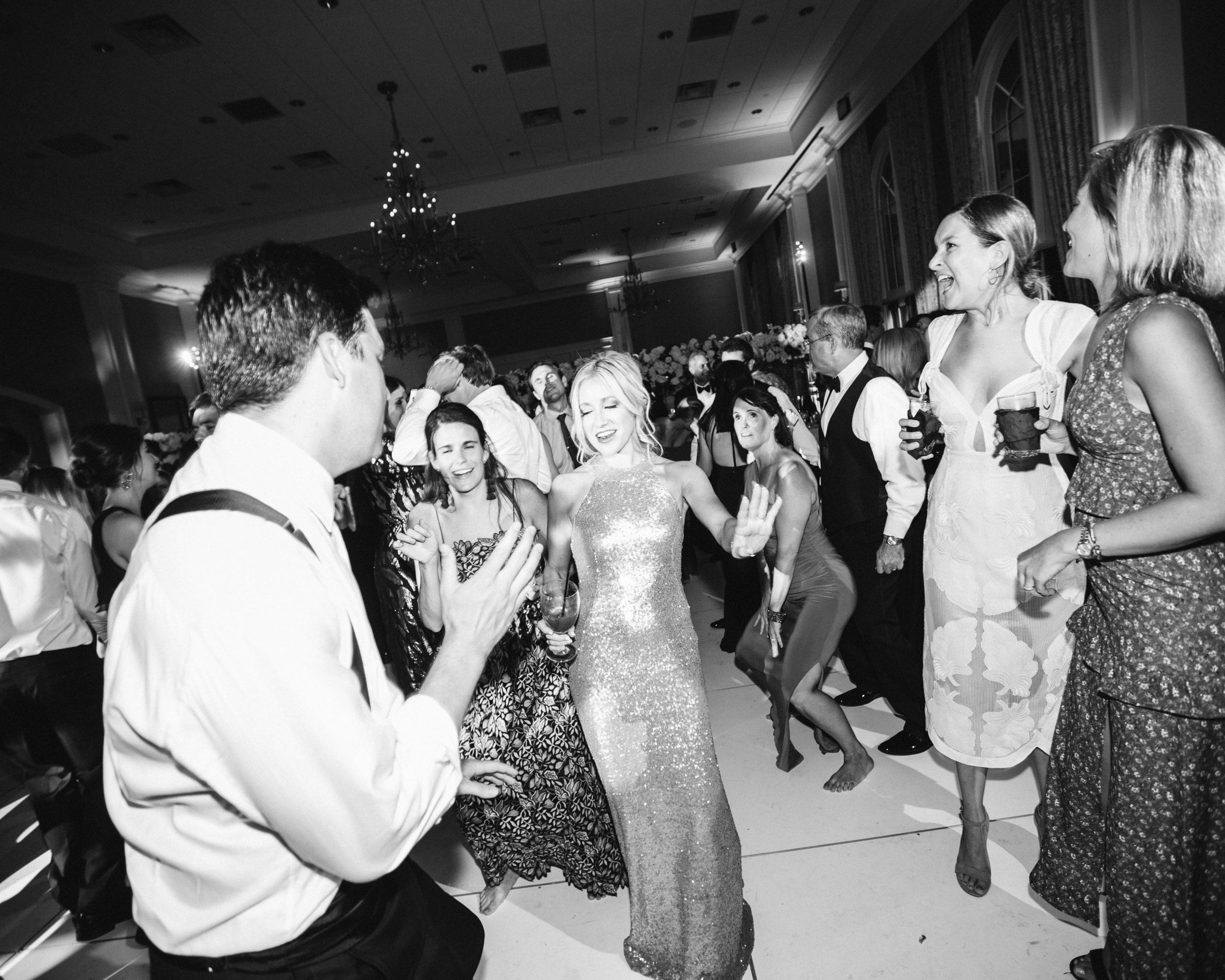 Black and white image of a crowd dancing at a wedding to illustrate wedding guest etiquette